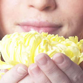 Woman smelling a yellow flower